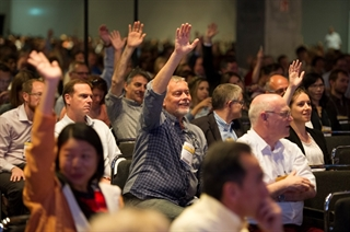 Attendees raise their hands at a presentation at the International Congress in Berlin, Germany.